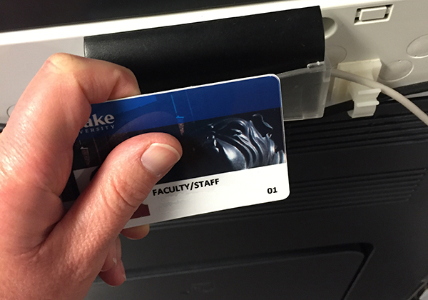 Image of tapping ID card on the side of a printer